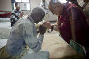 Его Святейшество Далай-лама здоровается с пожилым пациентом во время посещения нового отделения в офтальмологическом научном центре им. Раджендры Прасада при Индийском институте медицинских наук (AIIMS) в Нью-Дели, Индия. 10 марта 2013 г. Фото: Тензин Чойджор (офис ЕСДЛ).