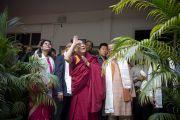 Его Святейшество Далай-лама машет рукой вышедшим, чтобы приветствовать его, студентам Индийского института управления. 11 марта 2013 г. Мирут, штат Уттар-Прадеш, Индий. Фото: Тензин Чойджор (офис ЕСДЛ).