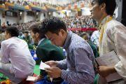 Студент записывает свой вопрос к Его Святейшеству Далай-ламе в первый день учений в Тибетской детской деревне. Дхарамсала, Индия. 27 июня 2013 г. Фото: Тензин Чойджор (офис ЕСДЛ)