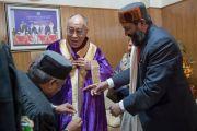Его Святейшество Далай-лама облачается в докторскую мантию Центрального университета штата Химачал Прадеш перед началом торжественной церемонии вручения дипломов. Шимла, штат Химчал Прадеш, Индия. 19 марта 2014 г. Фото: Тензин Чойджор (офис ЕСДЛ)