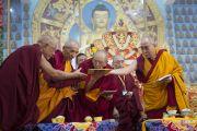 Его Святейшество Далай-лама раздает старшим монахам программы церемонии, посвященной 55-летию со дня первых учений, дарованных им в изгнании в Таванге. Мундгод, Индия. 26 декабря 2014 г. Фото: Тензин Чойджор (офис ЕСДЛ)
