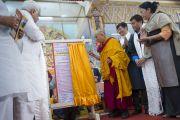 Его Святейшество Далай-лама открывает доску, часть проекта министерства туризма штата Карнатака, предназначенного в помощь посетителям тибетских поселений, во время церемонии, посвященной 55-летию со дня первых учений, дарованных Далай-ламой в изгнании в Таванге. Мундгод, Индия. 26 декабря 2014 г. Фото: Тензин Чойджор (офис ЕСДЛ)