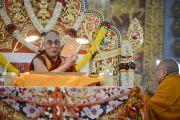 Его Святейшество Далай-лама представляет собравшимся антологию важнейших текстов по буддийской науке об уме в четвертый день учений в монастыре Ганден Джангце. Мундгод, Индия. 26 декабря 2014 г. Фото: Тензин Чойджор (офис ЕСДЛ)