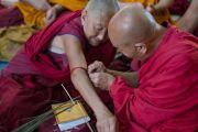 Монах помогает своему товарищу завязать защитный шнурок во время подготовки к посвящению Гухьясамаджи, дарованному Его Святейшеством Далай-ламой в тантрическом монастыре-университете Гьюто. Сидбхари, Химачал-Прадеш, Индия. 11 мая 2015 г. Фото: Тензин Чойджор (офис ЕСДЛ)