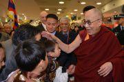 Его Святейшество Далай-лама приветствует тибетцев, собравшихся в аэропорту, чтобы встретить своего духовного лидера. Сидней, Австралия. Фото: Джереми Рассел (офис ЕСДЛ)