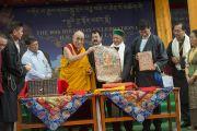 Его Святейшество Далай-лама и главный министр штата Химачал-Прадеш представляют собравшимся комплекты репродукций и книг во время праздничных торжеств по случаю 80-летия тибетского духовного лидера. Дхарамсала, Индия. 22 июня 2015 г. Фото: Тензин Чойджор (офис ЕСДЛ)