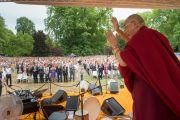 Его Святейшество Далай-лама приветствует 12-тысячную аудиторию, собравшуюся послушать его лекцию в висбаденском Курпарке. Висбаден, Гессен, Германия. 12 июля 2015 г. Фото: Мануэль Бауэр