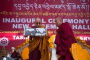 Во время торжественной церемонии освящения нового зала собраний в монастыре Ташилунпо Его Святейшество Далай-лама показывает собравшимся альбом с фотографиями, на которых он запечатлен с Панчен-ламой. Билакуппе, штат Карнатака, Индия. 19 декабря 2015 г. Фото: Тензин Чойджор (офис ЕСДЛ)