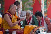 Дээрхийн Гэгээнтэн Далай Лам номын айлдвараа эхлэхийн өмнө Жамба Галдангийн намтрыг өгүүлсэн номын нээлт хийлээ. Энэтхэг, Карнатака, Билакуппе, Дашлхүнбо хийд. 2015.12.25. Гэрэл зургийг Тэнзин Чойжор (ДЛО)