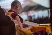 Его Святейшество Далай-лама читает текст во время учений по 18 коренным текстам и комментариям традиции Ламрим в монастыре Ташилунпо. Билакуппе, штат Карнатака, Индия. 25 декабря 2015 г. Фото: Тензин Чойджор (офис ЕСДЛ)