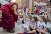 По дороге в актовый зал Его Святейшество Далай-лама шутит с маленькими учениками, вышедшими встречать его во двор школы. Нью-Дели, Индия. 8 апреля 2016 г. Фото: Тензин Чойджор (офис ЕСДЛ)