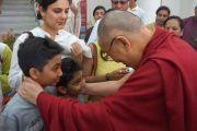 Его Святейшество Далай-лама приветствует своих молодых почитателей у входа на выставку фотографий Виджая Кранти в галерее Всеиндийского общества изящных искусств и ремесел. Нью-Дели, Индия. 10 апреля 2016 г. Фото: Джереми Рассел (офис ЕСДЛ)