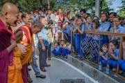 Его Святейшество Далай-лама шутливо приветствует тибетских школьников, собравшихся во дворе главного тибетского храма на торжества по случаю праздника Весак – дня рождения, просветления и ухода в паринирвану Будды Шакьямуни. Дхарамсала, Индия. 21 мая 2016 г. Фото: Тензин Чойджор (офис ЕСДЛ)