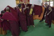 Монахи помогают друг другу облачиться в одеяния полностью посвященных монахов во время церемонии в храме Дрепунг Лачи. Мундгод, штат Карнатака, Индия. 2 июля 2016 г. Фото: Тензин Чойджор (офис ЕСДЛ)