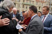 Его Святейшество Далай-лама подписывает книгу одному из своих почитателей, направляясь на встречу в министерство культуры. Прага, Чехия. 18 октября 2016 г. Фото: Оливье Адам