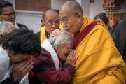 Его Святейшество Далай-лама тепло приветствует пожилую тибетскую женщину, направляясь к месту учений, чтобы принять участие в подготовительных ритуалах для посвящения Калачакры. Бодхгая, штат Бихар, Индия. 6 января 2017 г. Фото: Тензин Чойджор (офис ЕСДЛ)