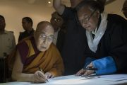 Его Святейшество Далай-лама ставит автограф на одной из работ мастера тибетской каллиграфии Джамьянга Дордже. Раджгир, штат Бихар, Индия. 17 марта 2017 г. Фото: Тензин Чойджор (офис ЕСДЛ)