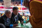 Монахи раздают гостям, сидящим на сцене, пилюли долгой жизни во время посвящения долгой жизни Белой Тары, даруемого Его Святейшеством Далай-ламой. Бомдила, штат Аруначал-Прадеш, Индия. 5 апреля 2017 г. Фото: Тензин Чойджор (офис ЕСДЛ)