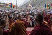 В конце второго дня учений по сочинению Камалашилы «Ступени созерцания» Его Святейшество Далай-лама машет рукой на прощание верующим, прячущимся под зонтиками от небольшого дождя. Дискет, долина Нубра, штат Джамму и Кашмир, Индия. 12 июля 2017 г. Фото: Тензин Чойджор (офис ЕСДЛ)