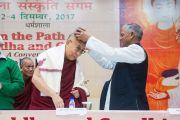 Его Святейшеству Далай-ламе преподносят в дар традиционную накидку и шапочку «химачали топи» в начале конференции, посвященной вопросам мира во всем мире. Дхарамсала, Индия. 2 декабря 2017 г. Фото: Лобсанг Церинг.