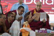 В ходе лекции в Тумкурском университете Его Святейшество Далай-лама представляет книги, подготовленные и опубликованные монастырем Сера Чже. Тумкур, штат Карнатака, Индия. 26 декабря 2017 г. Фото: Тензин Чойджор.