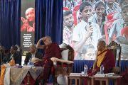 Его Святейшество Далай-лама заслоняет глаза рукой от яркого света прожекторов, чтобы лучше рассмотреть студента, задающего ему вопрос во время лекции в Тумкурском университете. Тумкур, штат Карнатака, Индия. 26 декабря 2017 г. Фото: Тензин Чойджор.