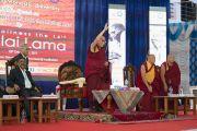 Поднявшись на сцену, Его Святейшество Далай-лама приветствует слушателей перед началом лекции в Тумкурском университете. Тумкур, штат Карнатака, Индия. 26 декабря 2017 г. Фото: Тензин Чойджор.