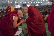 Поднявшись на сцену в начале празднования золотого юбилея Центрального института высшей тибетологии, Его Святейшество Далай-лама приветствует Тхрангу Ринпоче. Сарнатх, Варанаси, Индия. 1 января 2018 г. Фото: Тензин Пунцок.
