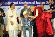 Его Святейшество Далай-лама вручает одному из лауреатов награду «Дживан Гаурав Пураскар» за выдающийся вклад в дело образования в ходе церемонии открытия Второго национального конгресса учителей. Пуна, штат Махараштра, Индия. 10 января 2018 г. Фото: Лобсанг Церинг.