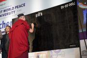 Его Святейшество Далай-лама в традиционной индийской учительской шапочке пишет на доске советы для учителей и школьников во время церемонии открытия Второго национального конгресса учителей. Пуна, штат Махараштра, Индия. 10 января 2018 г. Фото: Лобсанг Церинг.
