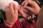 Верующие повязывают друг другу на руки красные нити-обереги во время предварительных ритуалов, необходимых для посвящений, которые будет даровать Его Святейшество Далай-лама. Бодхгая, штат Бихар, Индия. 18 января 2018 г. Фото: Мануэль Бауэр.