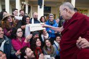 По прибытии в главный тибетский храм Его Святейшество Далай-лама приветствует иностранных паломников и паломниц, одна из которых держит в руках табличку с приветствием на тибетском языке. Дхарамсала, Индия. 5 марта 2018 г. Фото: Тензин Чойджор.
