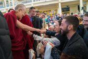 Покидая главный тибетский храм по завершении встречи с более чем 600 иностранными паломниками, Его Святейшество Далай-лама останавливается, чтобы пожать руки участникам встречи. Дхарамсала, Индия. 5 марта 2018 г. Фото: Тензин Чойджор.