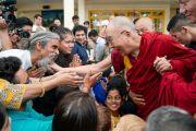 Возвращаясь в свою резиденцию по завершении встречи с туристами из Индии и других стран мира, Его Святейшество Далай-лама шутливо приветствует одного из участников встречи. Дхарамсала, Индия. 19 мая 2018 г. Фото: Тензин Чойджор.