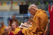 Его Святейшество Далай-лама рассматривает один из буклетов, которые были предоставлены организаторами всем участникам учений для стран Балтии и России. Рига, Латвия. 16 июня 2018 г. Фото: Тензин Чойджор.