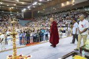Поднявшись на сцену стадиона «Тьягарадж», Его Святейшество Далай-лама приветствует более 5000 учителей, собравшихся на церемонии запуска учебной программы «Счастье» для школ Дели. Нью-Дели, Индия. 2 июля 2018 г. Фото: Тензин Чойджор.